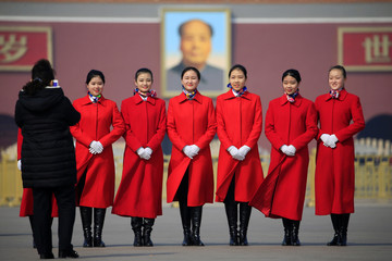Ushers pose for pictures in front of a portrait of former chairman Mao Zedong before the third plenary session of the Chinese People's Political Consultative Conference (CPPCC) in Beijing