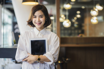 Young beautiful asian woman standing and holding tablet in office