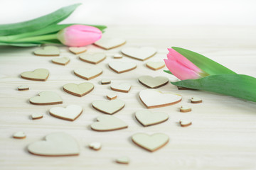 Couple of pink tulips on background of wooden hearts