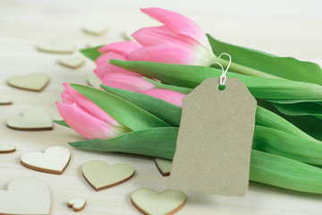 Spring desktop with pink tulips, craft lable and wooden hearts