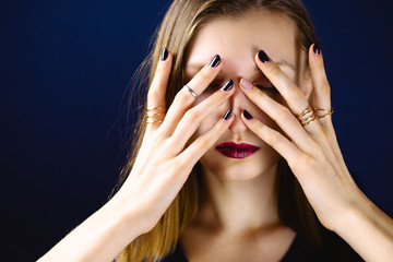 Portrait of young adult white woman wearing dark plum lipstick covering her face with her hands with dark manicure. Selective focus.