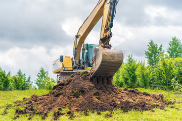 Excavator removes the grass layer