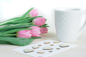 Tender desktop with pink tulips, ceramic mug and card with wooden hearts