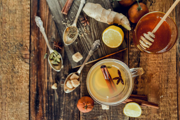 Vitamin tea with lemon and honey, ginger and spices on wooden background . The concept of spring beriberi and colds.
