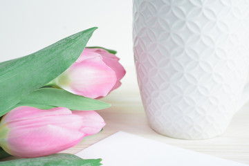 Soft composition with white ceramic mug and pink tulips