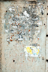 The sand-colored plaster on the wall with torn scraps of old paper ads in which recognizable only single letters, grunge texture background, vertical