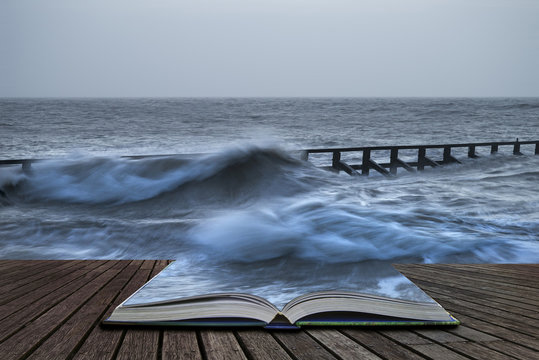 Beautiful dramatic stormy landscape image of waves crashing onto beach at sunrise in pages of book