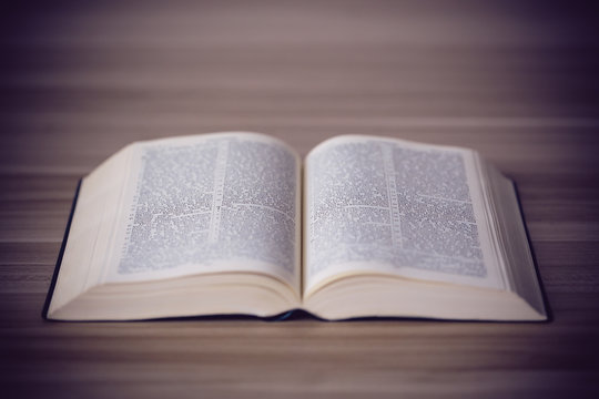 An opened holy bible on a wooden table