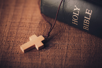 Close-up Shot Of Cross And Bible On The Old Wooden Table