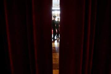 Military delegates are seen between curtains during the third plenary session of the Chinese People's Political Consultative Conference (CPPCC) at the Great Hall of the People in Beijing