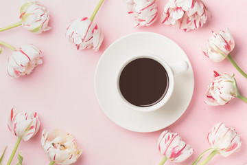 Spring morning concept. Flat-lay of cup of coffee and flowers over light pink background, top view with space for your text