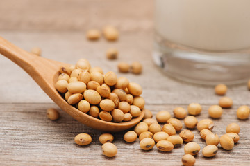 Soy beans in spoon on wooden background