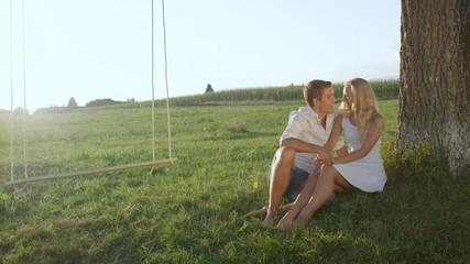 Young couple gazing at each other sitting under a tree in a meadow conversing