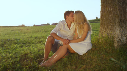CLOSE UP: Beautiful young couple kissing under a tree in beautiful green meadow