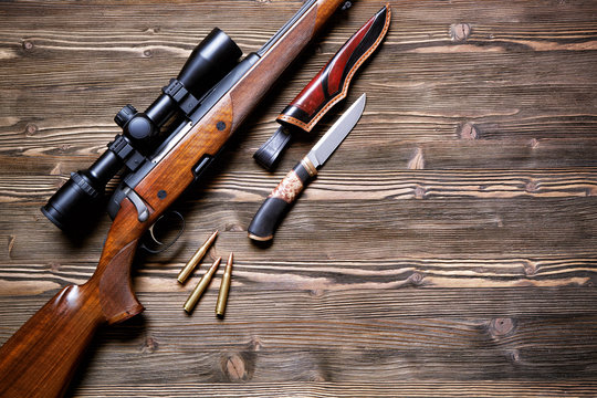Hunting equipment on old wooden background.