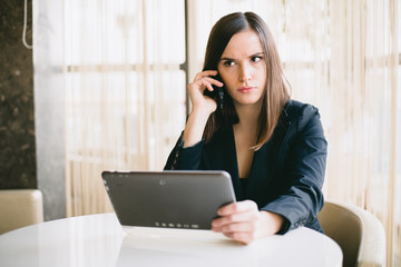 Serious young businesswoman talking on the phone in office