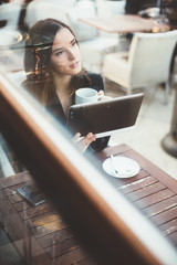 Daydreaming millennial business woman on coffee break