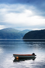 boat on water fjord with mountains in Norway
