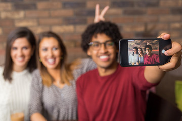 Group of friends taking a selfie in a restaurant cafe