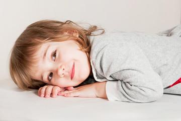 Portrait of little baby girl lies on light floor