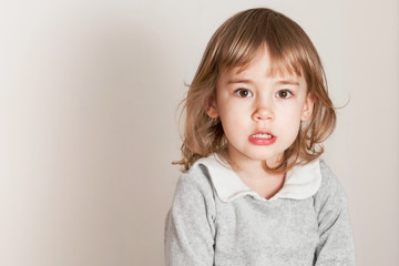Unhappy little baby girl on light background