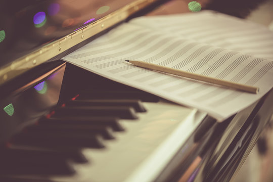 Compose Concept. Pencil and sheet music on the piano keyboard
