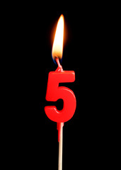 Burning candle in the form of five figures (numbers, dates) for cake isolated on black background. The concept of celebrating a birthday, anniversary, important date, holiday, table setting