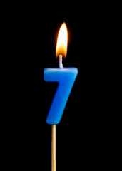 Burning candle in the form of seven figures (numbers, dates) for cake isolated on black background. The concept of celebrating a birthday, anniversary, important date, holiday, table setting