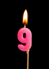 Burning candle in the form of nine figures (numbers, dates) for cake isolated on black background. The concept of celebrating a birthday, anniversary, important date, holiday, table setting