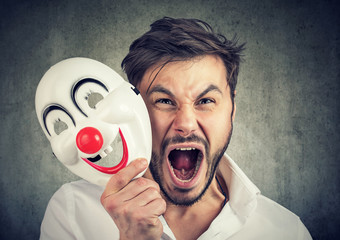 angry screaming man taking off a clown mask