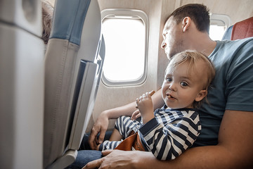 Man with little adorable boy on knees sitting near window in plane flying.
