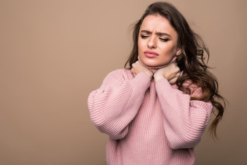 Young woman with sore throat isolated on brown background