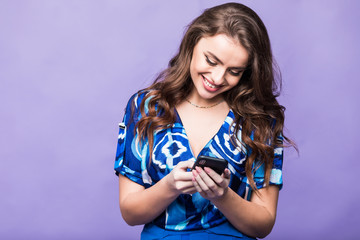 Smiling young woman thinking and using phone isolated on purple background