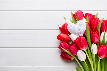 Springt time. Red tulip bouquet on the white wooden background.