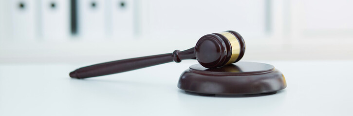 Brown wooden judge gavel lies on a wooden plate on white table.