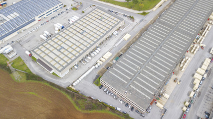 Perpendicular aerial view of a warehouse and its roof. In the parking lot some trucks and vans load and unload the products. Around there are trees and green land.