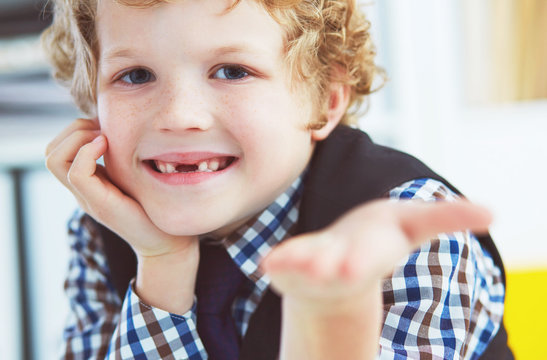 Litle caucasian boy holds a dropped milk tooth between his fingers and laughs looking into the camera.