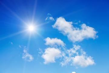 Голубое небо с большими пушистыми и белыми облаками и солнечными лучами