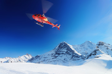 Red helicopter flying Swiss Alpine mountain Mannlichen in winter