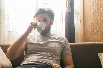 Young man sitting on sofa in living room and drinking coffee