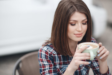 Portrait of beautiful smiling young white middle eastern Caucasian girl woman with long hair, brunette,sitting at table looking in camera. Woman with cup of coffee, tea outside on summer day.