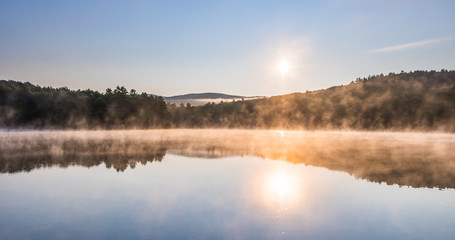 Gorgeous sunrise over pond with mountain views panorama