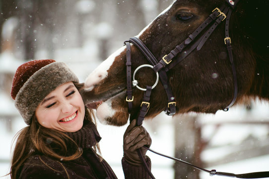 Female rider and horse in the open air. portrait of a beautiful young woman with her stallion, outdoors in winter