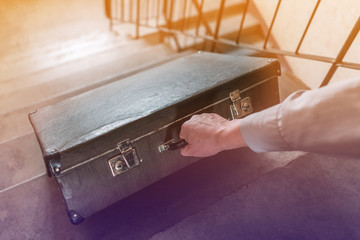 The man's hand drags a retro suitcase