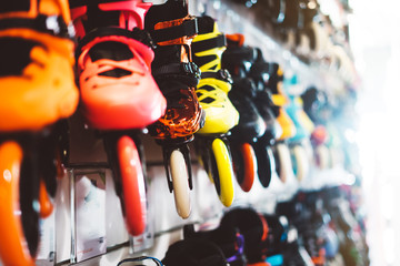 Assortment roller skates isolated in store shop, person choosing and buy color roller-skates on backgraund sun flare, healthy and activity lifestyle concept close up, sport footwear for rollerblade