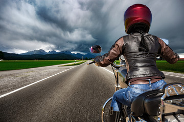 Fototapete - Biker girl on a motorcycle hurtling down the road in a lightning storm - Forggensee and Schwangau, Germany Bavaria