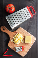 Grater, tomato and cutting board with grated cheese on wooden background