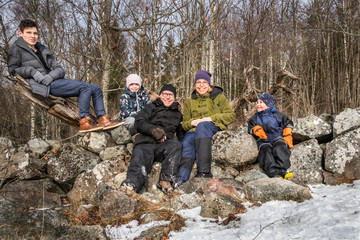 Winter family portrait outdoors. Parents and children leaning against a stone wall.
