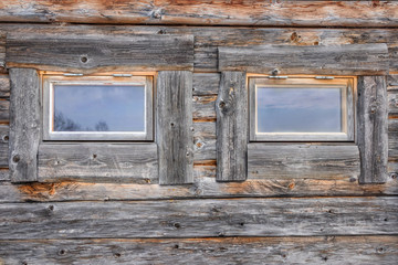 Front view of two windows on a weathered and aged log cabin.