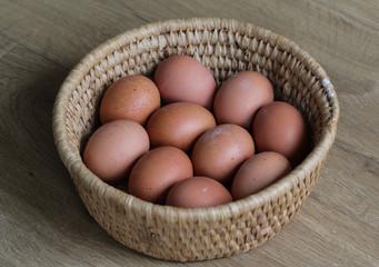 Brown chicken eggs in straw basket on wooden background in kitchen